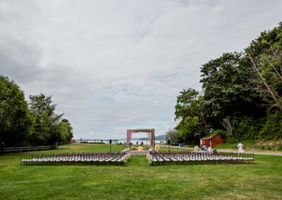 Setting up chairs and a floral arch for a wedding ceremony on the Meadow.