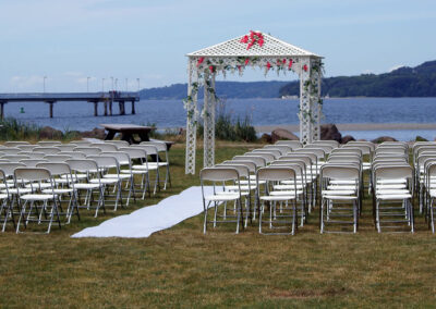 Wedding ceremony chairs, aisle, and flower-covered pergola on the Meadow near the waterfront in Des Moines.