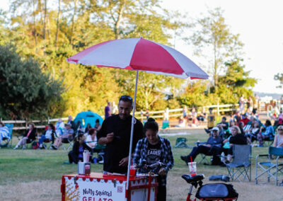 Attendees at a community event enjoy treats from an ice cream cart. Food trucks welcome.