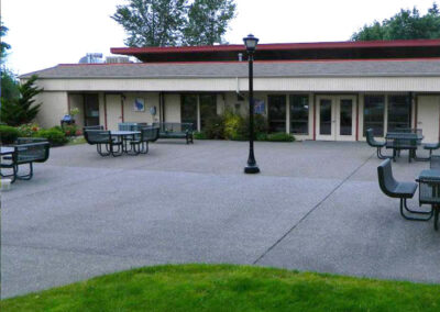 The 2,500 sq. ft. patio is surrounded by grass, mature trees, and a lovely rose garden.