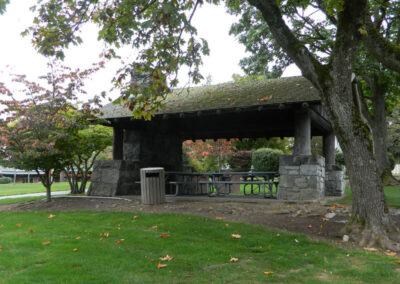 The picnic shelter is surrounded by grass and mature trees.